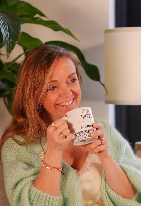 Julie Vermylen, souriante, une tasse d ethé à la main, habillée aux couleurs du printemps