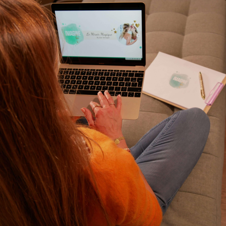 Julie de dos, assise en train de travailler sur son ordinateur
